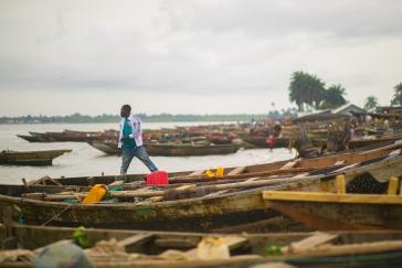 'Man in the midst of fishing boats back from the day's fishing.' Location: Ibeno Beach, Akwa Ibom, Nigeria. Photo Credit: Enefaa Thomas