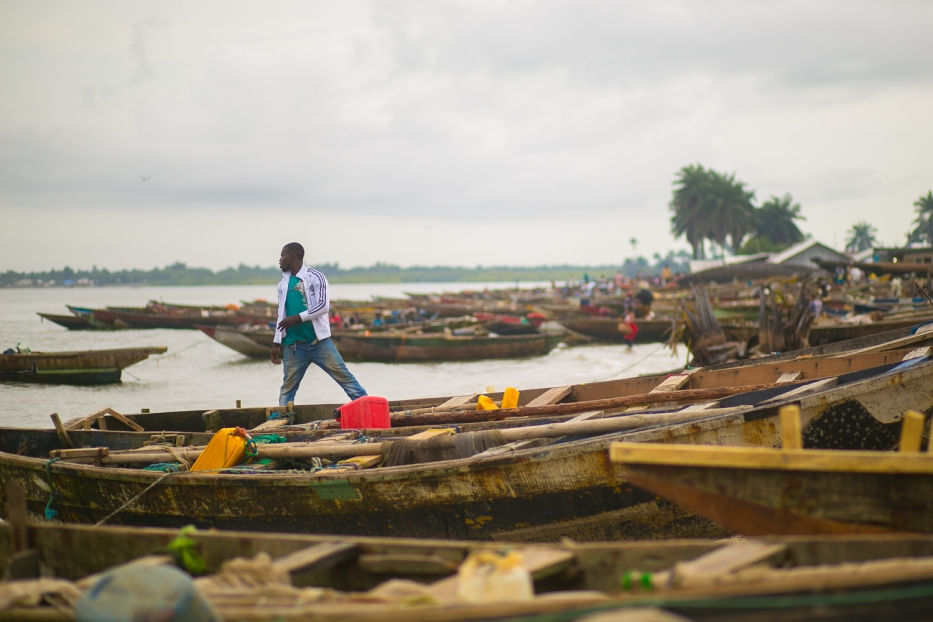 'Man in the midst of fishing boats back from the day's fishing.' Location: Ibeno Beach, Akwa Ibom, Nigeria. Photo Credit: Enefaa Thomas